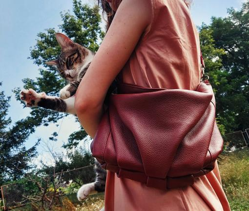 woman in a pink dress with a Koja leather clutch in a flower field holding a cat