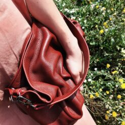 hand of a woman holding a leather clutch in a flower
